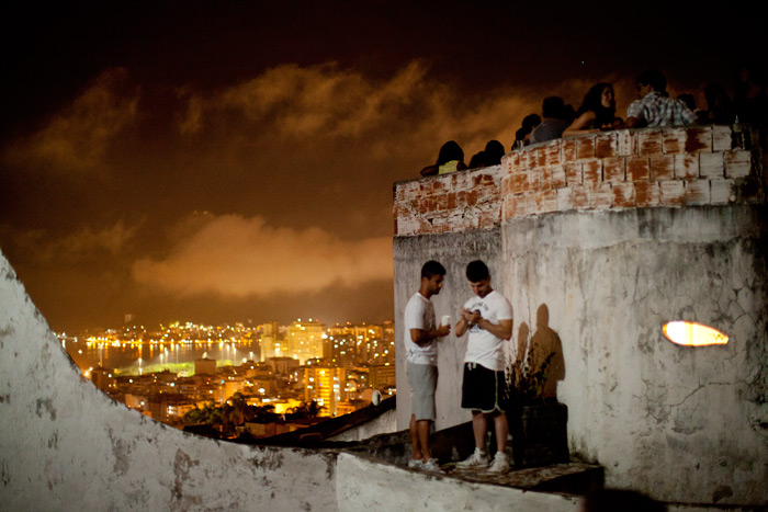 Favela dwellers gather on a roof above Rio's more conventional city districts