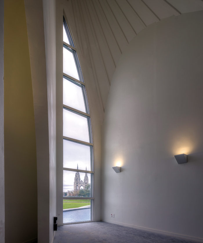 The organ room window reveals Saint- Jean des Vignes, seen above a water feature extending from the Cité. The door (left) echoes the window's shape