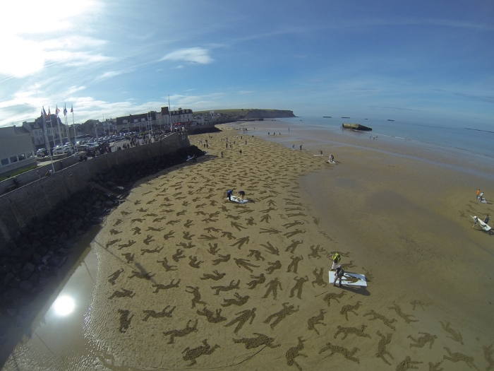 Andy Moss and Jamie Wardley's 2013 work The Fallen. Nine thousand silhouettes, representing the soldiers (on both sides) and civilians who died in the D-Day landings, were stencilled on to the sand at the D-Day landing beach of Arromanches on International Peace Day, September 2013