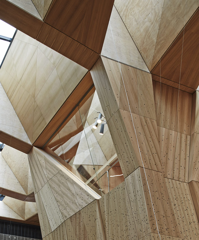 The ceiling comprises perforated plywood panels that dampen noise