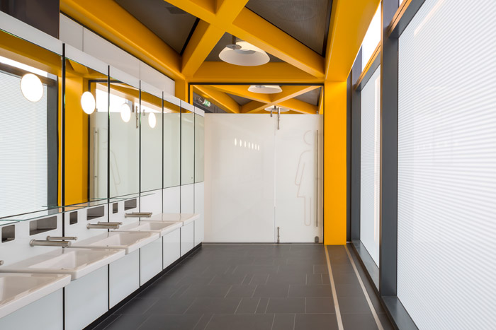 The north core yellow tables host washrooms. Beyond the door, this women's bathroom glazing appears red from the outside.
