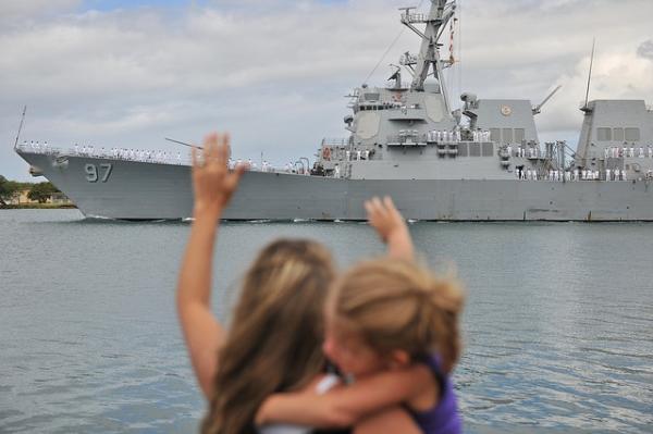 white people waving at an American warship