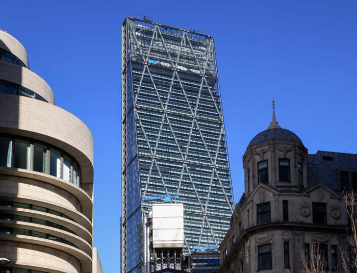 The megaframe is visible beneath exterior glazing. K-bracing and north core are behind. The tower of Lutyens' Midland Bank Building (1931) is in the foreground