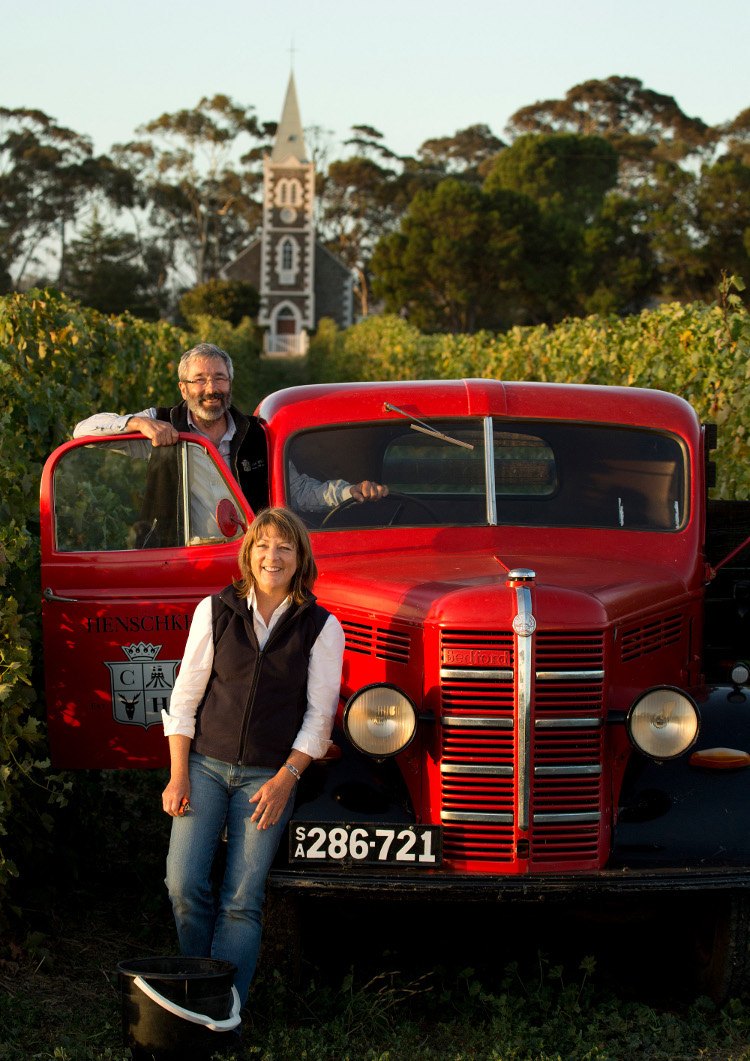 Stephen and Prue Henschke in their historic Hill of Grace vineyard, first planted in 1860, against the backdrop of the Lutheran church that gave the vineyard its name Photography courtesy of Henschke