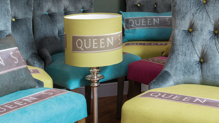 The Queen Street Collection was also designed for the Harington's Hotel, Bath, and which is inspired by the hotel's central location. Burghard used a photograph, taken of the street name outside the hotel, and then digitally manipulated it to include the hotel's branding colours to produce a range of lampshades, cushions and dining chairs as well as very large textile wall maps.