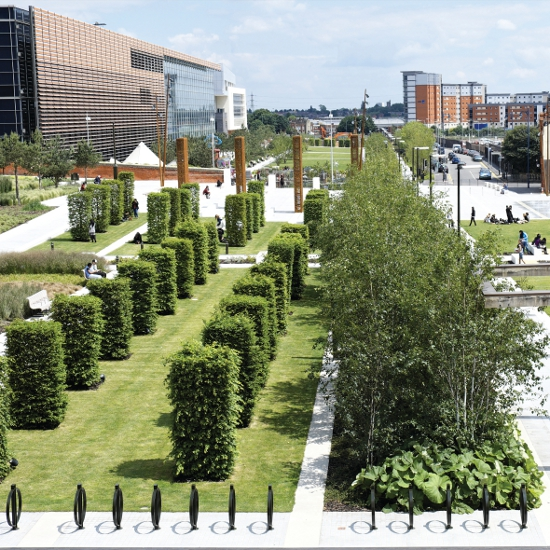 Public Space Schemes  Winner: Eastside City Park, Birmingham by Patel Taylor  Eastside City Park is Birmingham's first new park in 130 years. It is the focal point of the Eastside regeneration area, creating a setting for the surrounding buildings and green route into the district from the city centre. The park consists of a series of notional 'rooms' that are intended to be part of the city's network of physically well-defined public spaces. The main spaces in the park are City Park Square (an event area) and the eastern and western formal lawns, all linked by a spine path. These open spaces are edged by steel and precast concrete structures; groups of single species trees, both evergreen and deciduous; paving; and formal planting that is also arranged into single-species blocks. Within these edges, there are numerous smaller-scale spaces that have specific characteristics and numerous thresholds. The range of scales allows the park to function on both a civic and an individual level. The steel work is painted a very dark green, except for the weathering steel used for the lighting fins and columns in City Park Square that give that space a special characteristic. Prominent steel structures such as the pergolas, planting screens and the lighting fins all help to define the structure of the park. The lighting fins are sculptural features on the terraces of the square. Their height, colour and leaf-patterned cladding panels give them prominence as reference points within the park. They are internally lit from below, which highlights each one's subtly different cladding. The 3mx190m water feature is a strong part of the composition, defining the south-facing promenade. On its north edge there is a zone of Scots pines and iroko and steel seating. Summertime paddling is sure to be popular!  The judges said: 'At once formal and relaxed; skilfully unified' 'A lovely use of materials'