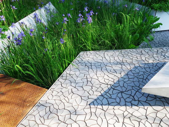 Surfaces  Cracked Earth by Hugo Bugg for KAZA Concrete  Debuting at this year's Chelsea Flower Show in Hugo Bugg's gold-medal winner, the RBC Waterscape Garden, Cracked Earth concrete floor tile highlighted an extraordinary bespoke floor surfacing solution set in an innovative and sustainable design environment. Hugo Bugg designed the Waterscape Garden to highlight global water issues by mimicking nature's way of slowing down water flow, featuring a seamless cracked-earth hard floor to establish the main theme. Drawing inspiration from the parched effects caused by extreme global weather, the design is layered with naturally occurring geometric patterns. KAzA Concrete, closely working with Bugg, designed the technical background and manufactured the seamless cracked-earth motif in form of refined and reinforced concrete mosaic tiles. Two types of mosaic-like element sets make the Cracked Earth pattern, each of 54 different small cracked-earth pieces. Each piece is individually manufactured, surface treated and applied to a carrier layer. This enables quick and easy installation without being permanently fixed to the ground, while creating a seamless arrangement. The Cracked Earth mosaic is an ideal surfacing solution for courtyards, terraces and walkways of contemporary commercial environments where the floor covering aims to leave visitors with a bold impression, raises questions and provides an even surface for walking on. Installation on internal and external vertical surfaces is also possible, with Cracked Earth serving as a nature-inspired contemporary feature wall, for example, in a museum or university campus. Bugg's colour choice of light grey adds a layer of weightlessness to the contemporary concept while showing how sustainable design can be elegant.  The judges said: 'Innovative, thought-provoking and practical – all the requisites of a winner' 'Practical but also aesthetically pleasing'